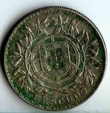 Moeda de 1 escudo de portugal com danos severos de pvc, vários escurecimentos e manchas verdes pela moeda.