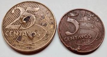 A esquerda uma moeda de vinte e cinco centavos e a direita uma de cinco centavos, ambas apresentam pequenas erosões resultado de oxidações, pequenos desgastes fortes, marcas de pedaços faltantes.